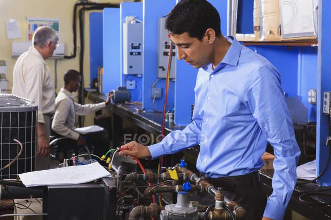 Студент вивчає систему керування, що підключається до печі в класі Хвац з одним студентом у інвалідному візку. — стокове фото
