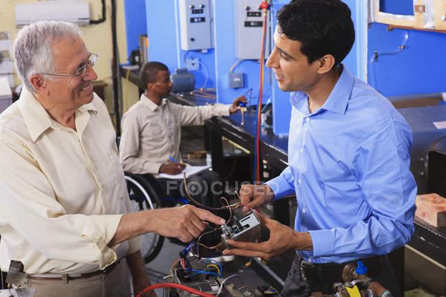 Учень, який вивчає систему керування електрикою на печі з професором у класі Хвац один студент у кріслі на колесах — стокове фото