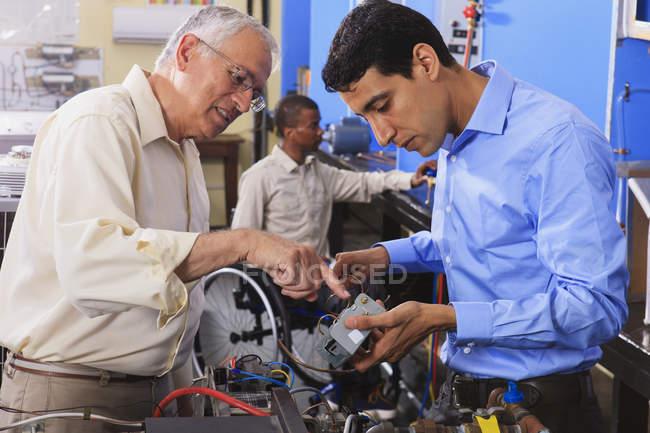 Étudiant examinant le système de commande électrique sur four avec professeur en classe CVC un étudiant en fauteuil roulant — Photo de stock
