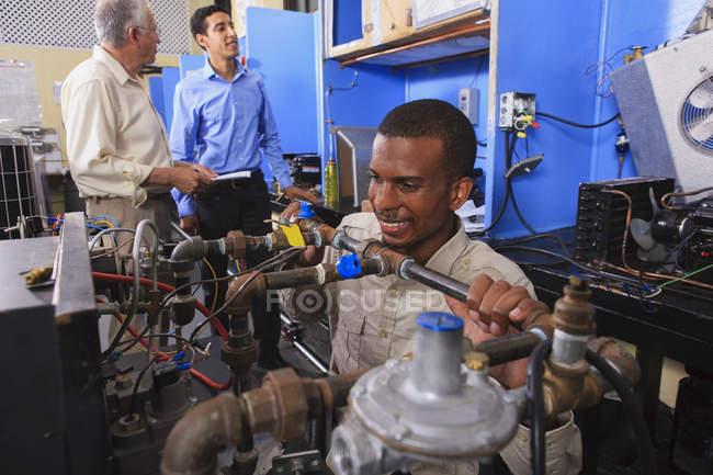 Étudiant en fauteuil roulant examinant les soupapes de commande de carburant sur four dans la salle de classe CVC — Photo de stock