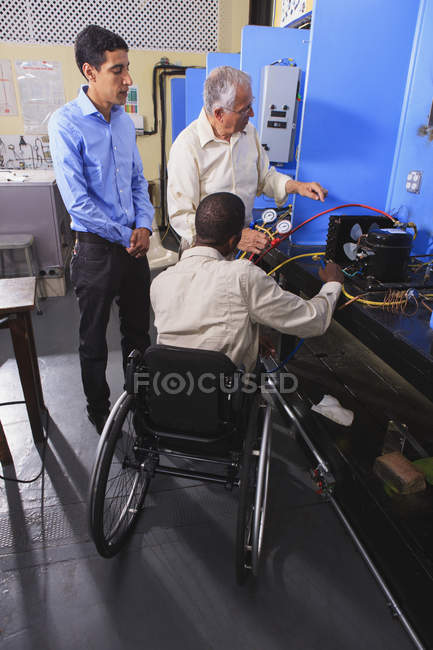 Інструктор обговорює кондиціонер, який заряджається з учнями в класі Хвац один студент у кріслі на колесах — стокове фото