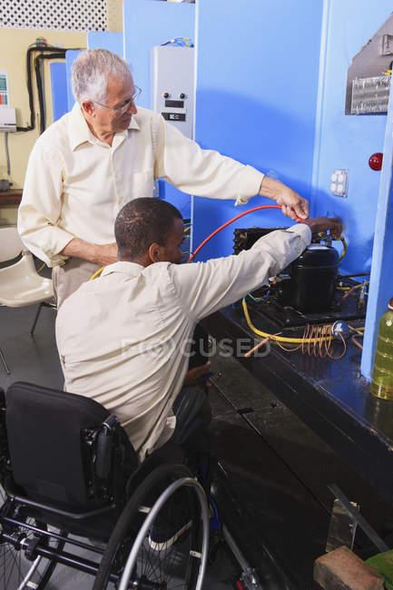 Інструктор обговорює кондиціонер, який заряджається зі студентом у кріслі на колесах у класі Хвац. — стокове фото