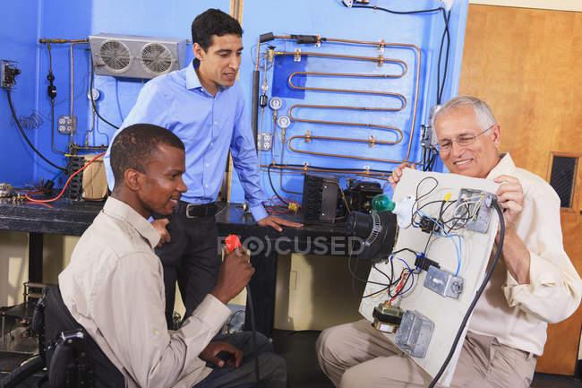 Інструктор демонструє систему керування кондиціонером на демо-дошці для студентів з Hvac класу один студент у інвалідному візку — стокове фото