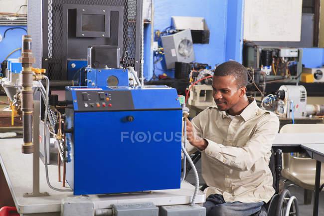 Étudiant en fauteuil roulant étudiant la conduite de carburant au gaz naturel sur le four dans la salle de classe CVC — Photo de stock