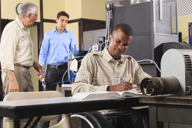 Інструктор обговорює контроль суміші палива для печі в класі Хвац, поки один студент в інвалідному візку робить нотатки — стокове фото