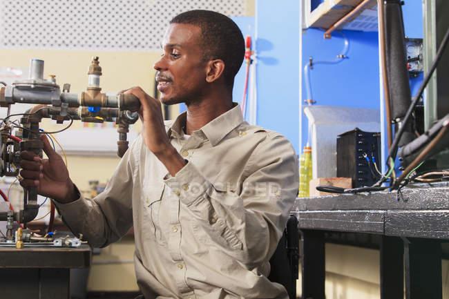 Étudiant en fauteuil roulant examinant les commandes de débit de carburant dans la salle de classe CVC — Photo de stock