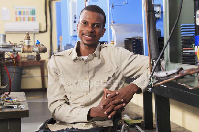 Étudiant en fauteuil roulant à côté des commandes de débit de carburant dans la salle de classe CVC — Photo de stock