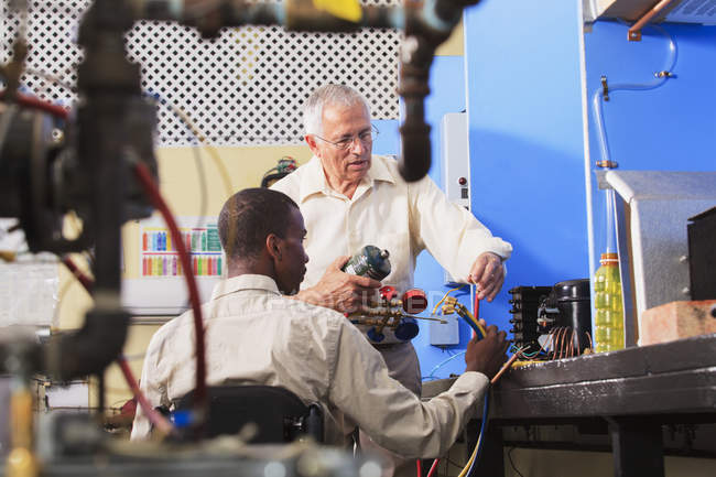 Instructor demonstrating air conditioner recharging manifold with gauges in HVAC classroom student in wheelchair — Stock Photo