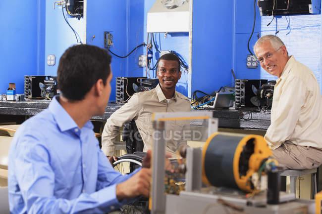 Студент створює експеримент з генератором в той час як інструктор обговорює систему Hvac для студента в інвалідному візку — стокове фото
