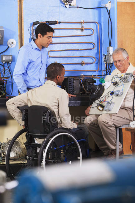 Instructor using demo board to explain HVAC control system operation one student in wheelchair — Stock Photo