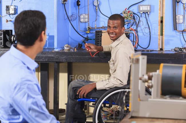 Студент в инвалидной коляске устанавливает HVAC эксперимент разговаривая с другим студентом — стоковое фото