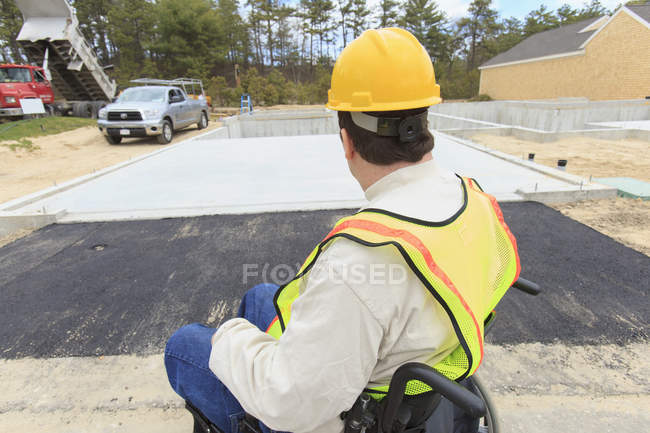 Construction supervisor with Spinal Cord Injury inspecting house foundation work — Fotografia de Stock