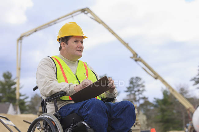 Construction supervisor with Spinal Cord Injury taking notes with concrete pump in background — стокове фото