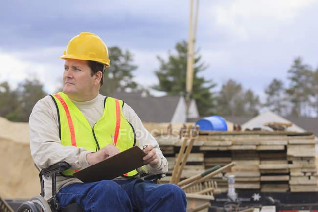Supervisor de construção com injúria de cabo espinhal tomando notas com formas de fundação de concreto em segundo plano — Fotografia de Stock