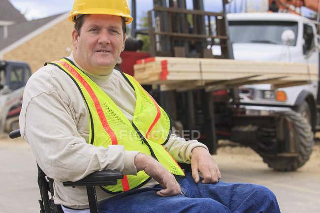 Construction supervisor with Spinal Cord Injury with forklift moving studs — Stock Photo