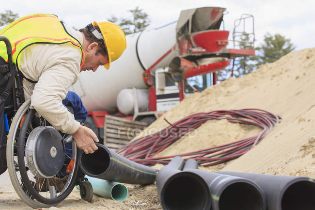 Construction supervisor with Spinal Cord Injury inspecting drainage pipes — Stock Photo