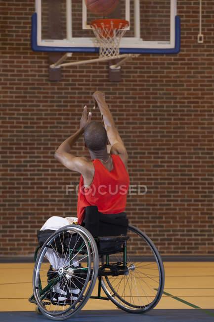 Man who had Spinal Meningitis in wheelchair taking a net shot in basketball — Stock Photo