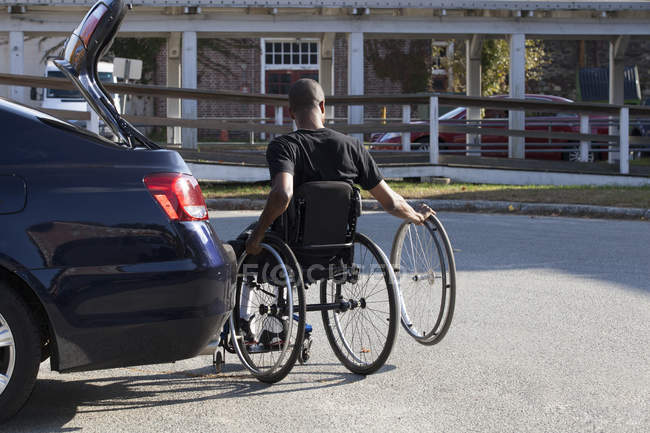 Hombre que tenía meningitis espinal en silla de ruedas entrando en su vehículo accesible - foto de stock