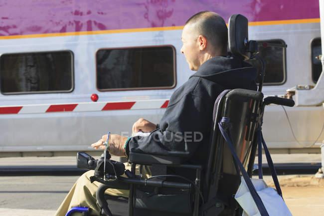Человек с травмой спинного мозга на моторизованном инвалидном кресле ждет общественного поезда — стоковое фото