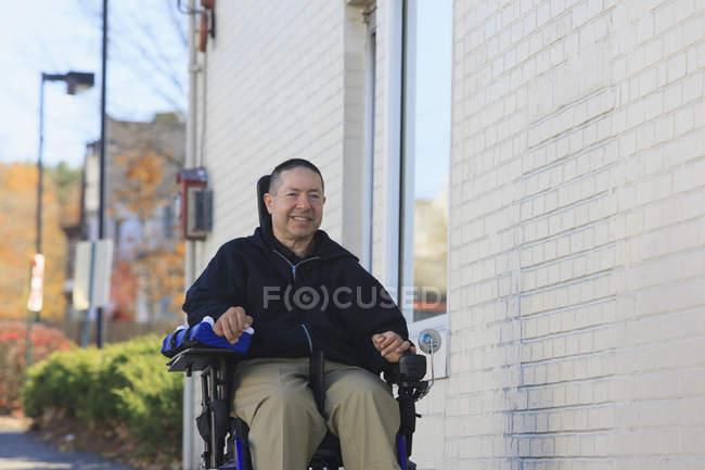 Homme avec lésion de la moelle épinière et bras avec lésions nerveuses dans un fauteuil roulant motorisé en utilisant une voie publique — Photo de stock