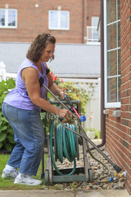 Woman with Spina Bifida using crutches and pulling garden hose — Stock Photo