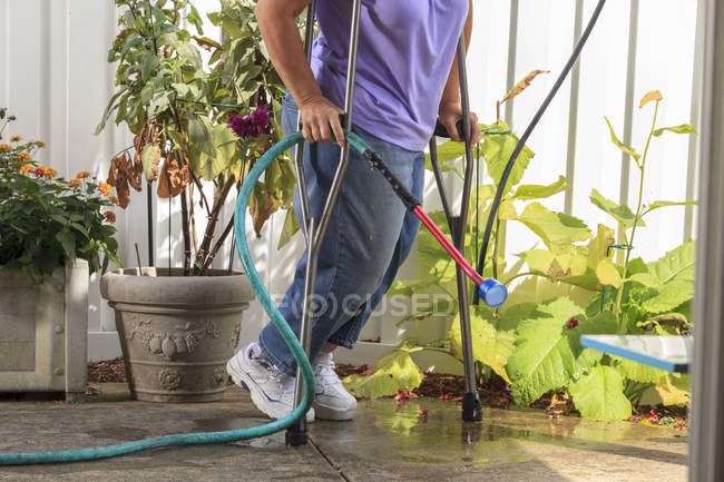 Woman with Spina Bifida walking with crutches and pulling garden hose — Stock Photo