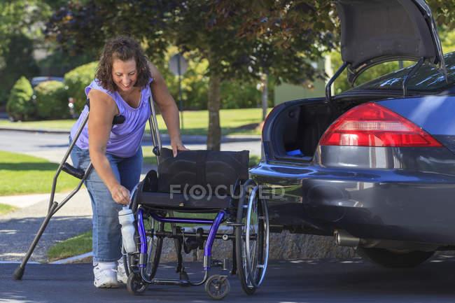 Женщина со Спиной Бифидой с помощью костылей разбирает инвалидное кресло на части для передвижения в машине — стоковое фото
