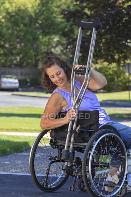 Женщина со спиной Бифида прикрепляет костыли к инвалидному креслу — стоковое фото