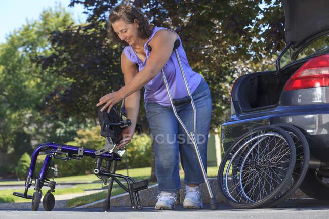 Mujer con Espina Bifida usando muletas para desmontar silla de ruedas para viajar en el coche - foto de stock