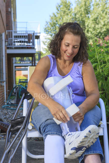 Mujer con Espina Bifida ajustando el soporte de la pierna - foto de stock