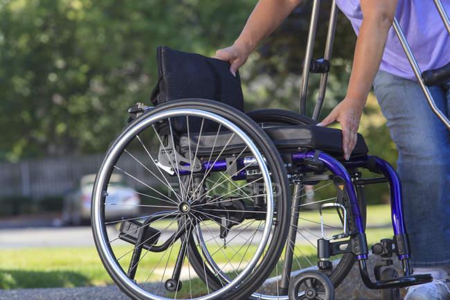 Жінка з Шпіною Біфідою за милицями складає інвалідний візок після подорожі в машині. — стокове фото