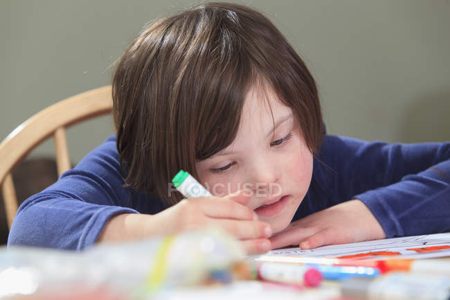 Child with Down Syndrome using coloring markers — стокове фото