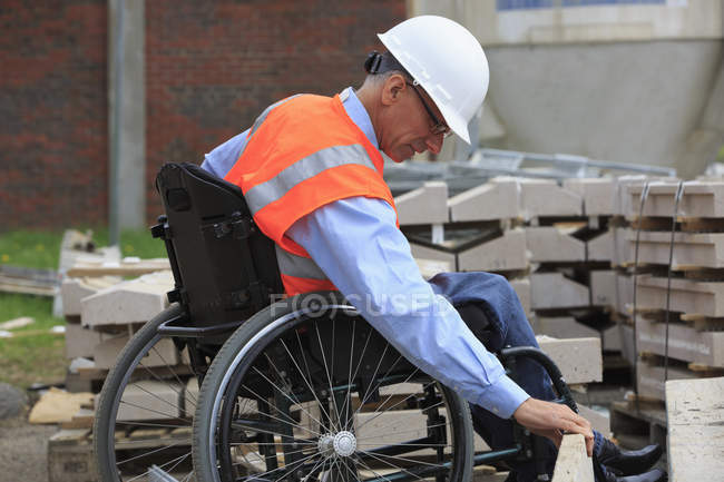 Project engineer with a Spinal Cord Injury in a wheelchair checking the site — Stock Photo