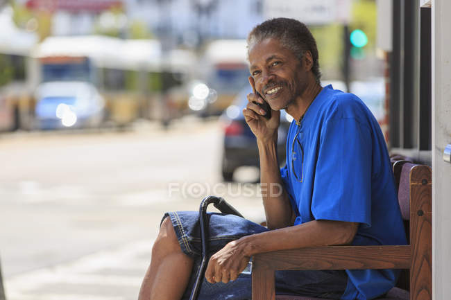 Man with Traumatic Brain Injury waiting at the bus terminal while on his phone — Stock Photo