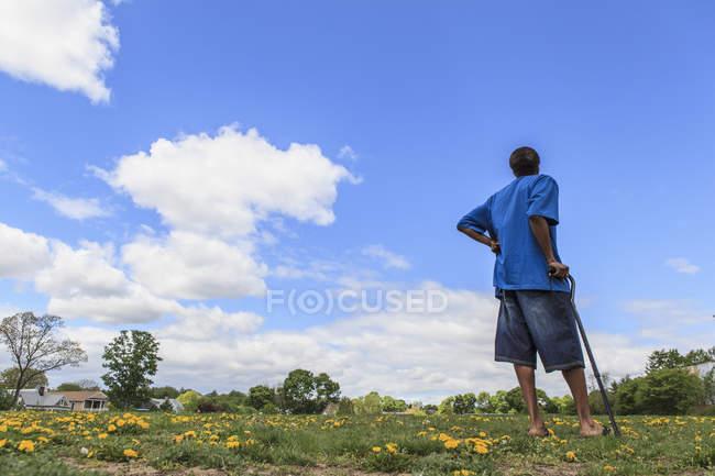 Uomo con Traumatica Ingiuria cerebrale in piedi in un campo di fiori — Foto stock