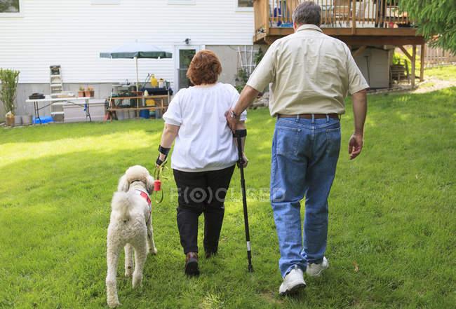 Жінка з РСД та її службовий собака ходять на задньому подвір