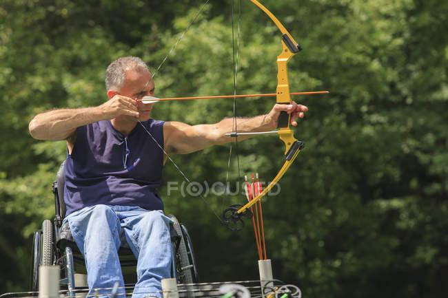 Человек с травмой спинного мозга в инвалидной коляске целится луком и стрелами для стрельбы из лука — стоковое фото