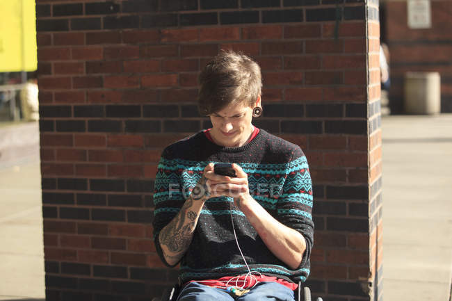 Trendy man with a spinal cord injury in wheelchair taking his text messages — Stock Photo
