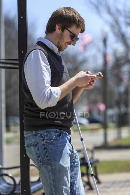 Юный слепой на автобусной остановке с помощью ассистивных технологий — стоковое фото