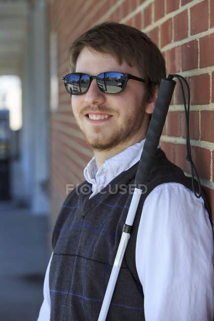 Молодой слепой человек с тростью — стоковое фото