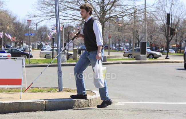 Joven ciego caminando en su vecindario después de ir de compras - foto de stock