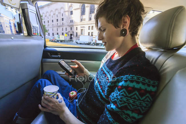 Trendy man with a spinal cord injury in wheelchair inside a taxi cab reading his text messages — Stockfoto
