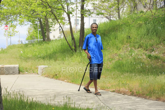 Homme avec traumatisme crânien faisant une promenade avec sa canne — Photo de stock