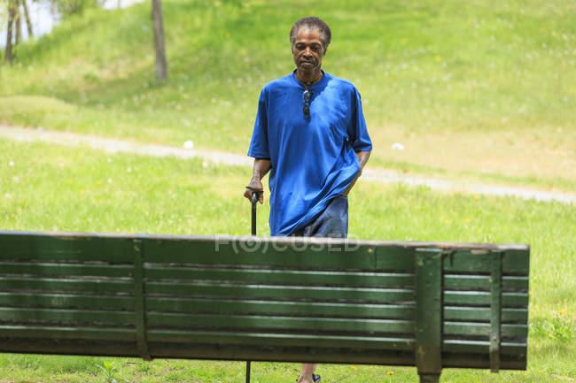Uomo con Traumatica Ingiuria cerebrale fare una passeggiata con la sua canna in un parco — Foto stock
