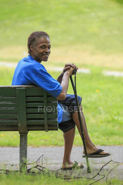 Uomo con Traumatica Ingiuria cerebrale rilassante con la sua canna in un parco — Foto stock