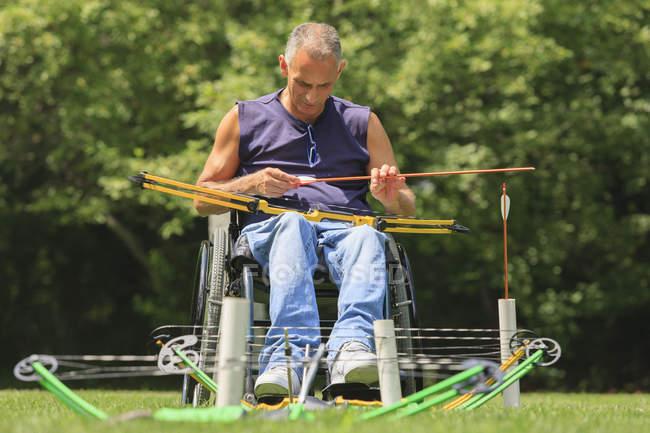 Человек с травмой спинного мозга в инвалидной коляске готовится к практике стрельбы из лука — стоковое фото