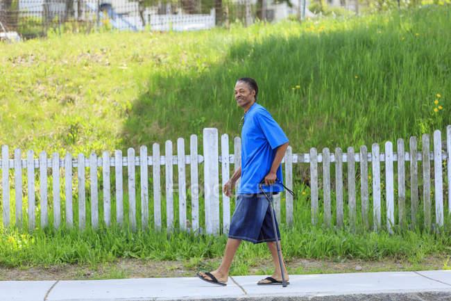 Hombre con lesión cerebral traumática relajándose con su bastón en su vecindario - foto de stock