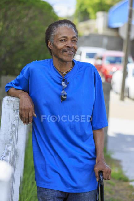 Uomo con Traumatica Ingiuria cerebrale rilassante con la sua canna nel suo quartiere — Foto stock