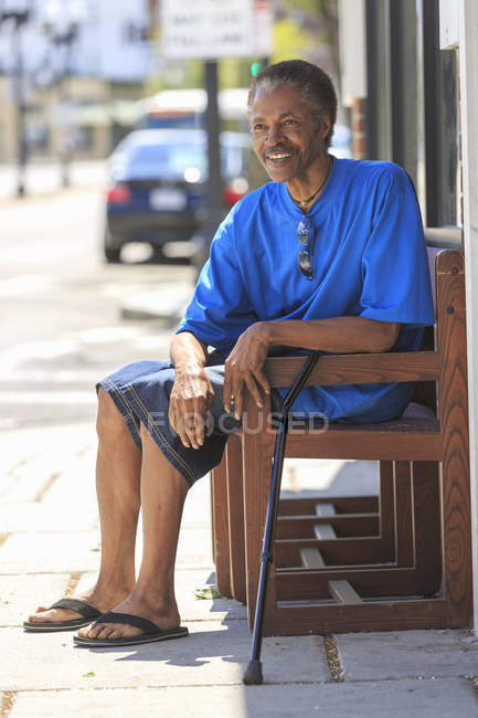 Man with Traumatic Brain Injury relaxing with his cane near the city street — Stock Photo