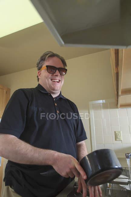 Hombre con ceguera congénita lavando platos en su cocina - foto de stock